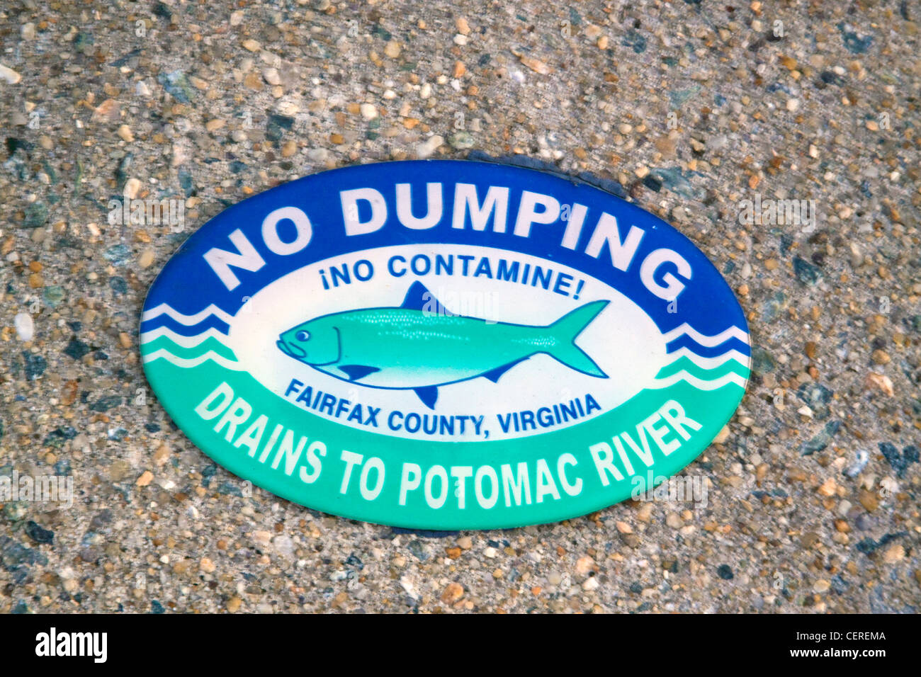 Fairfax County Virginia No Dumping Drains to Potomac River sign on top of a storm water drainage catch basin inlet - Stock Image