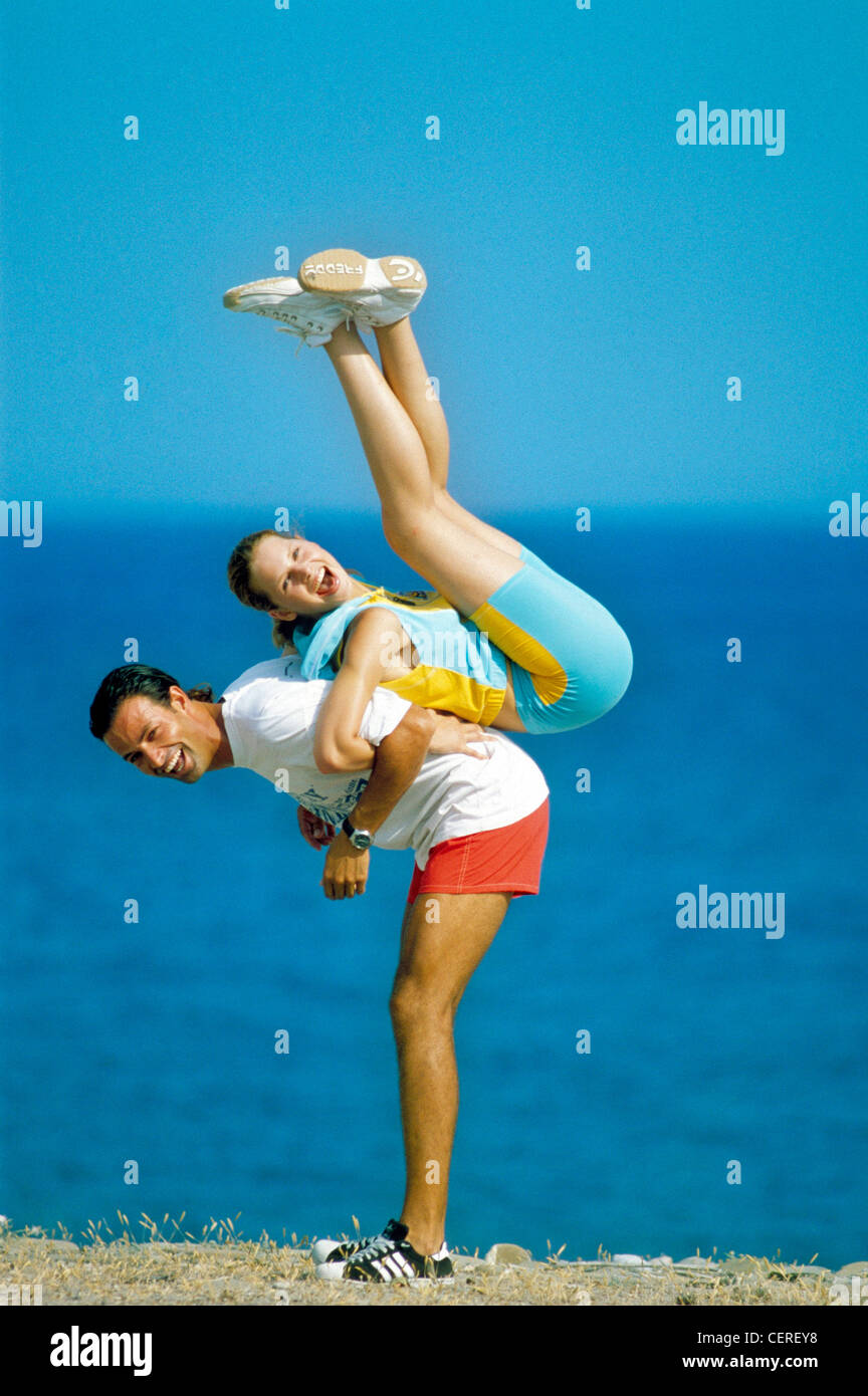 Couple on hill by sea Male lifting female up in air on his back linked arms Female dark blonde hair tied up wearing - Stock Image