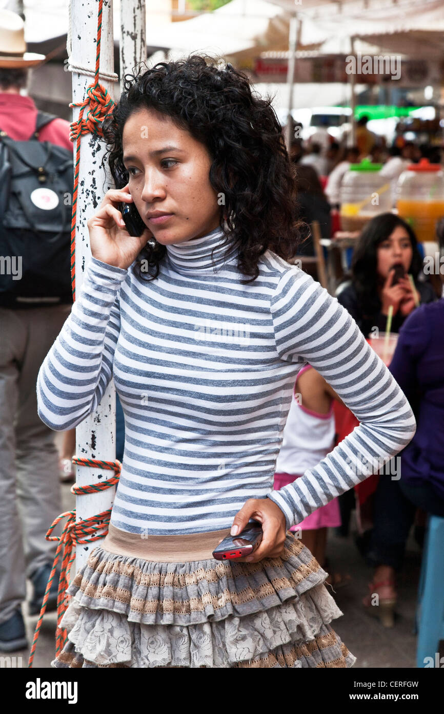 cute slim curly haired Mexican teenager with attitude in ruffled skirt talking on  cellphone at Friday market Llano - Stock Image