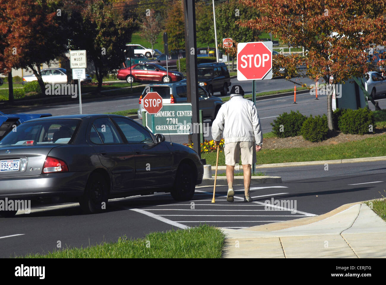 Senior citizen walks in a crosswalk while a car almost hits him - Greenbelt, Md - Stock Image