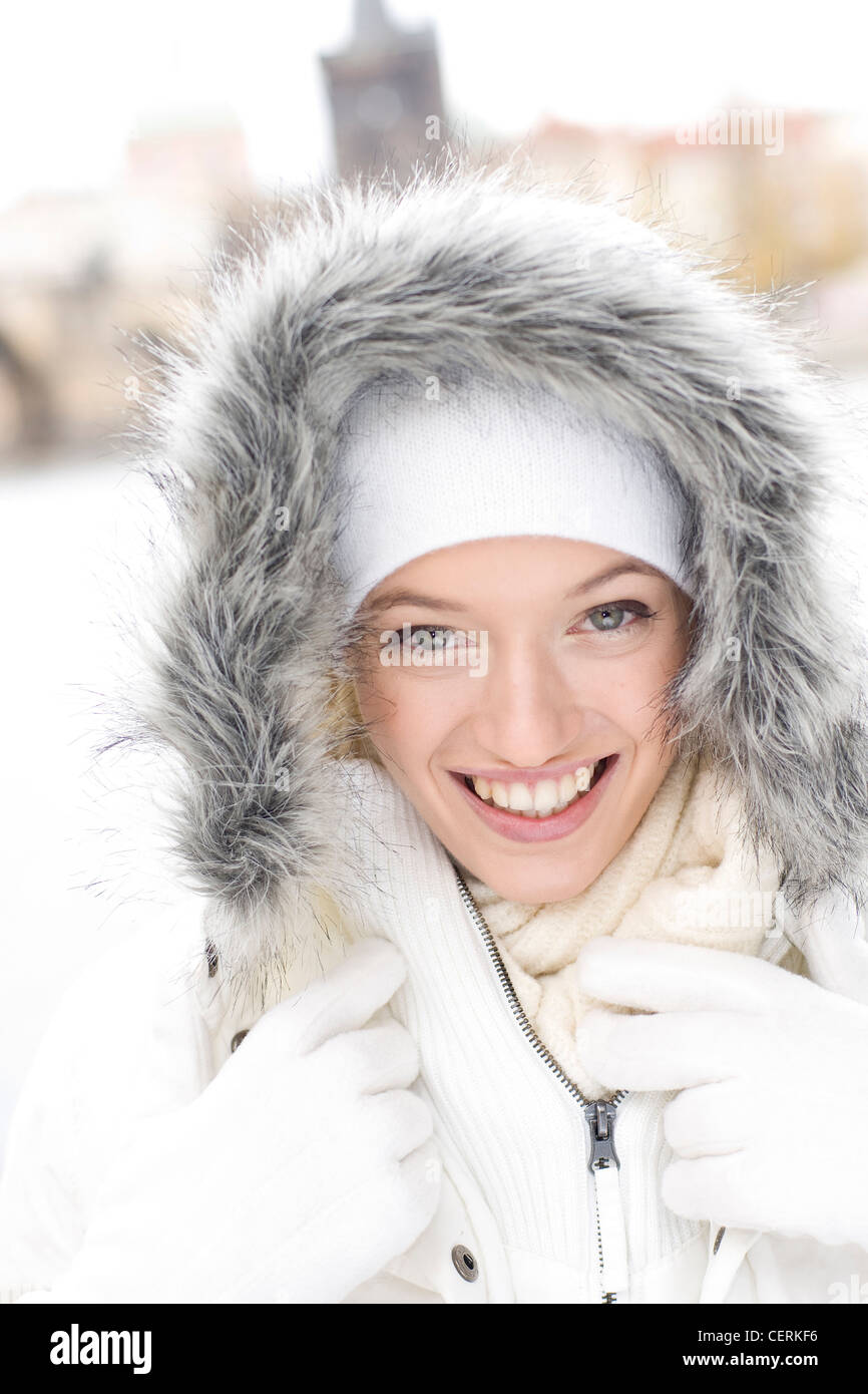 8b32d2914a1cbd Female dark blonde hair wearing white winter coat grey fur trimmed hood,  white wooly hat, white fleece gloves, cream scarf