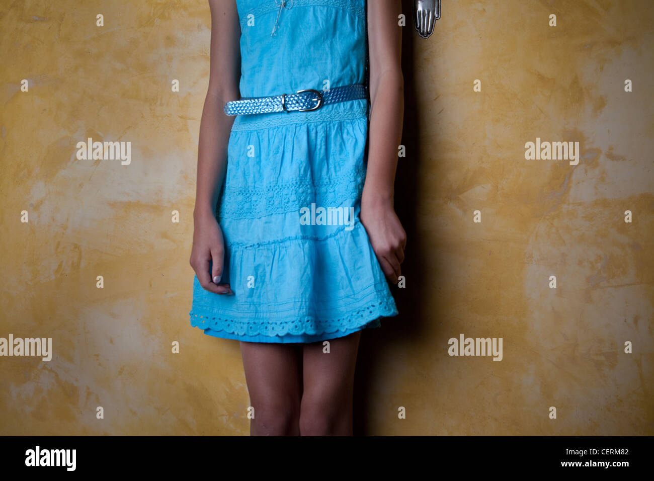 girl wearing blue dress standing against an adobe wall - Stock Image