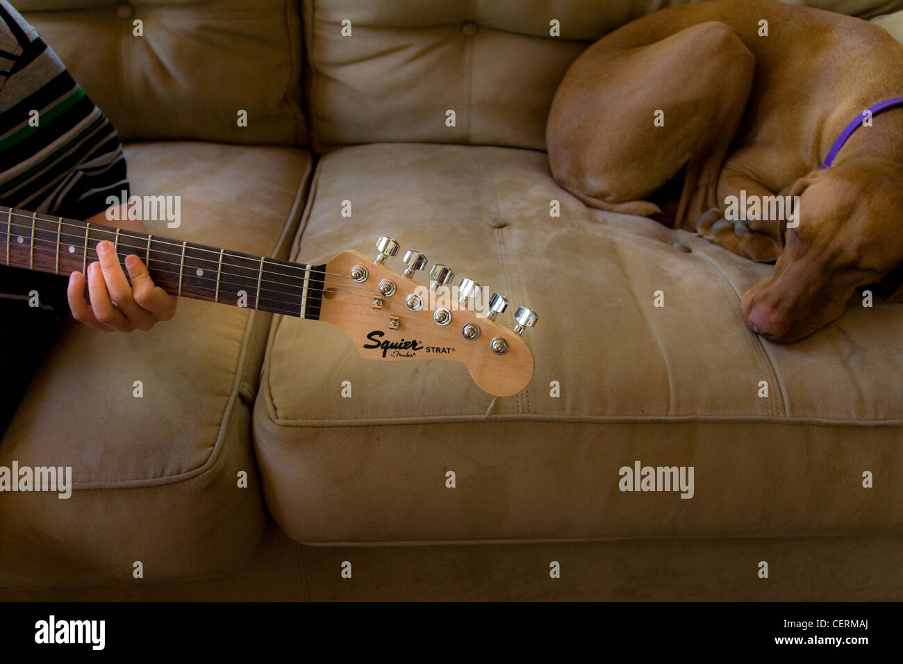 Boy playing his guitar while his dog sleeps next to him - Stock Image