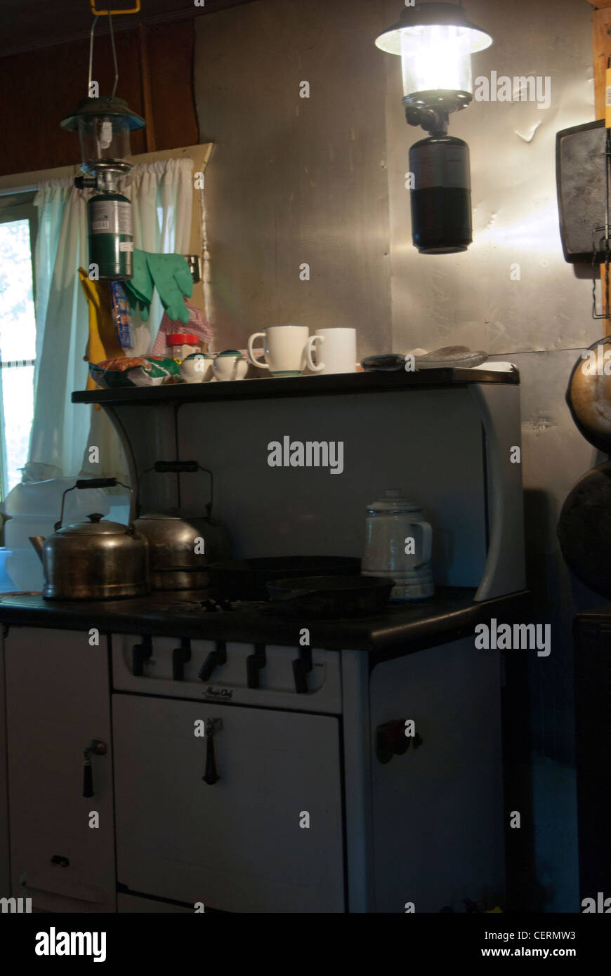 Old cabin stove with hanging lantern and vintage kettles. - Stock Image