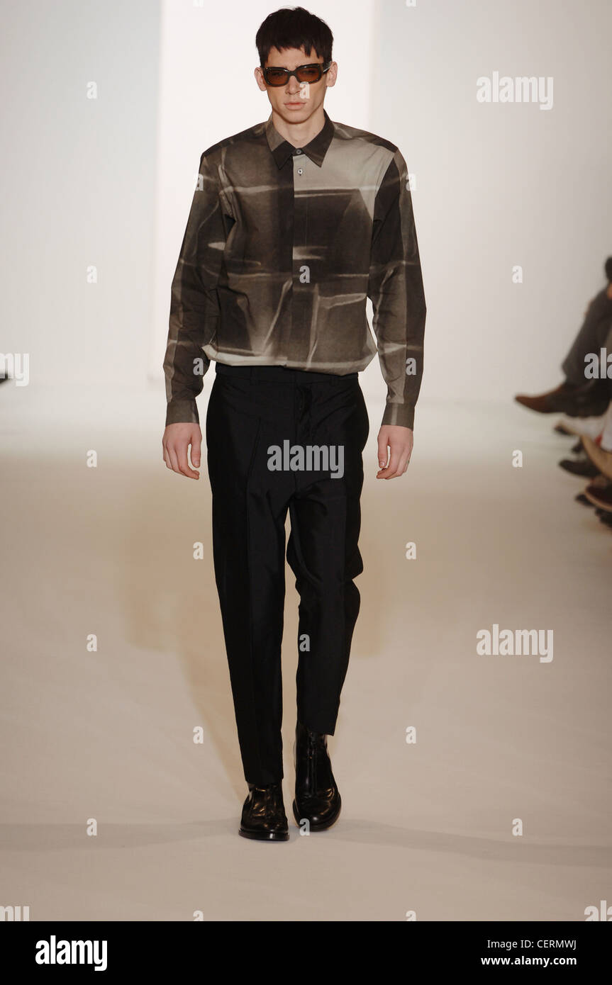 Marni Milan Ready to Wear Autumn Winter  Two tone print shirt and tapered black trousers, accessorized tinted shades - Stock Image