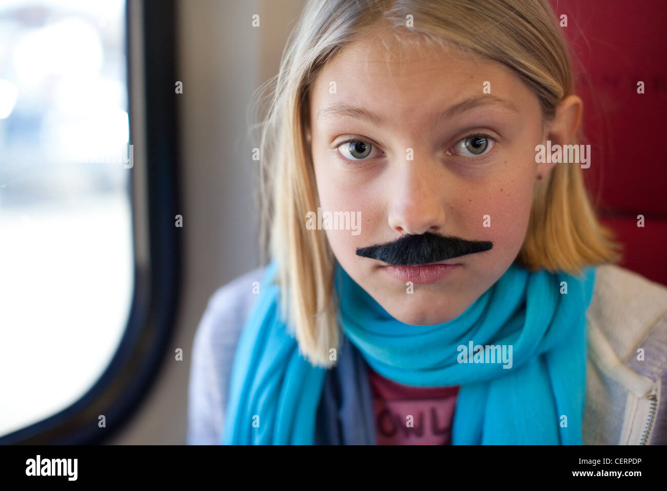 Ten year old girl wears a mustache. - Stock Image