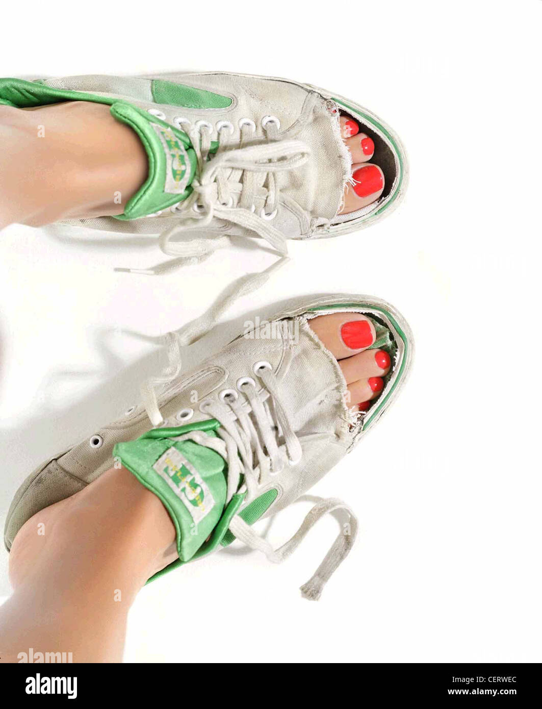 a497a355d388 Female wearing old green and white trainers with the toes cut out - Stock  Image