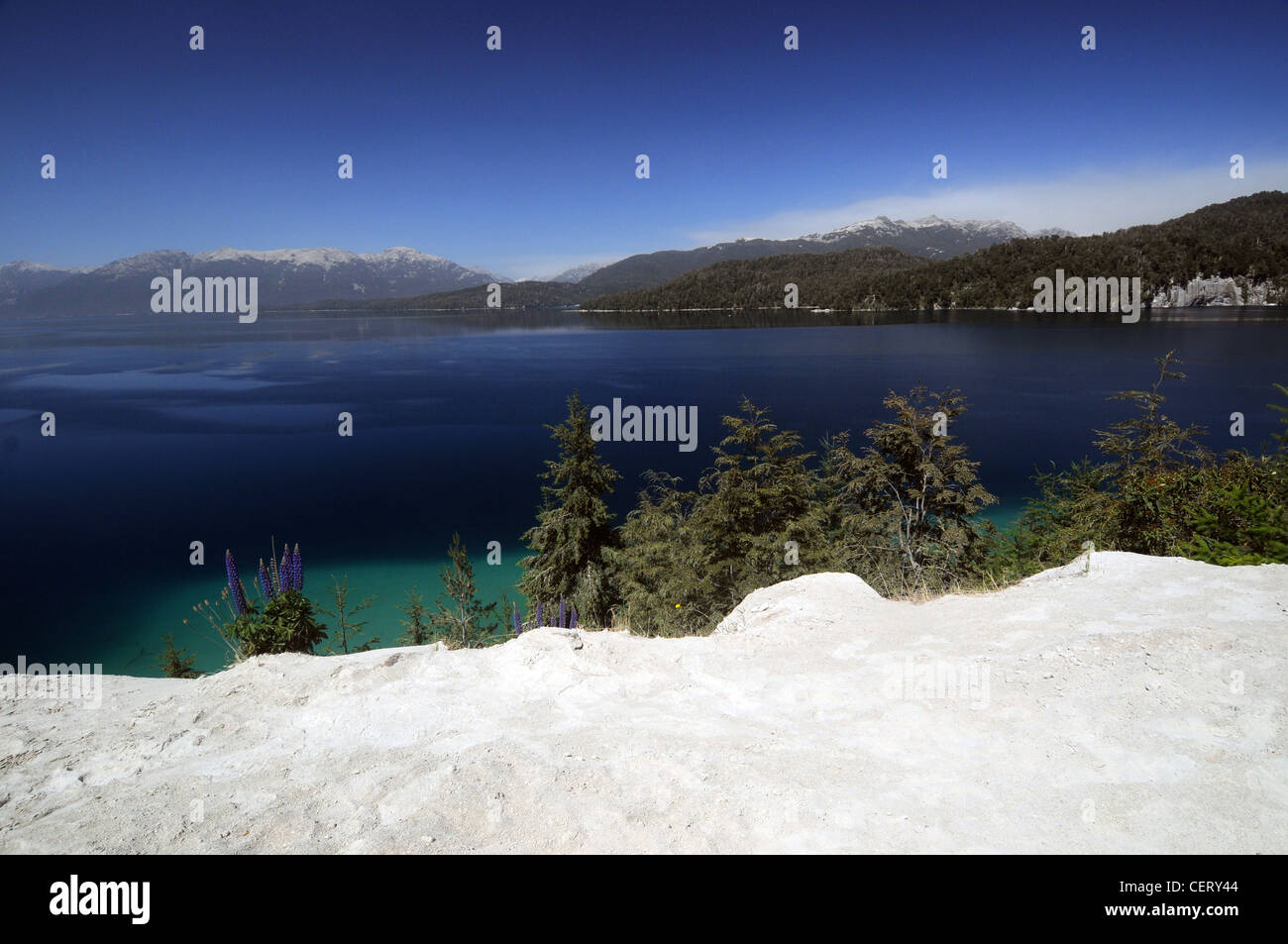 Ash on the shores of Lake Nahuel Huapi from eruptions of nearby Volcan Puyehue (plume visible on horizon), Patagonia, - Stock Image