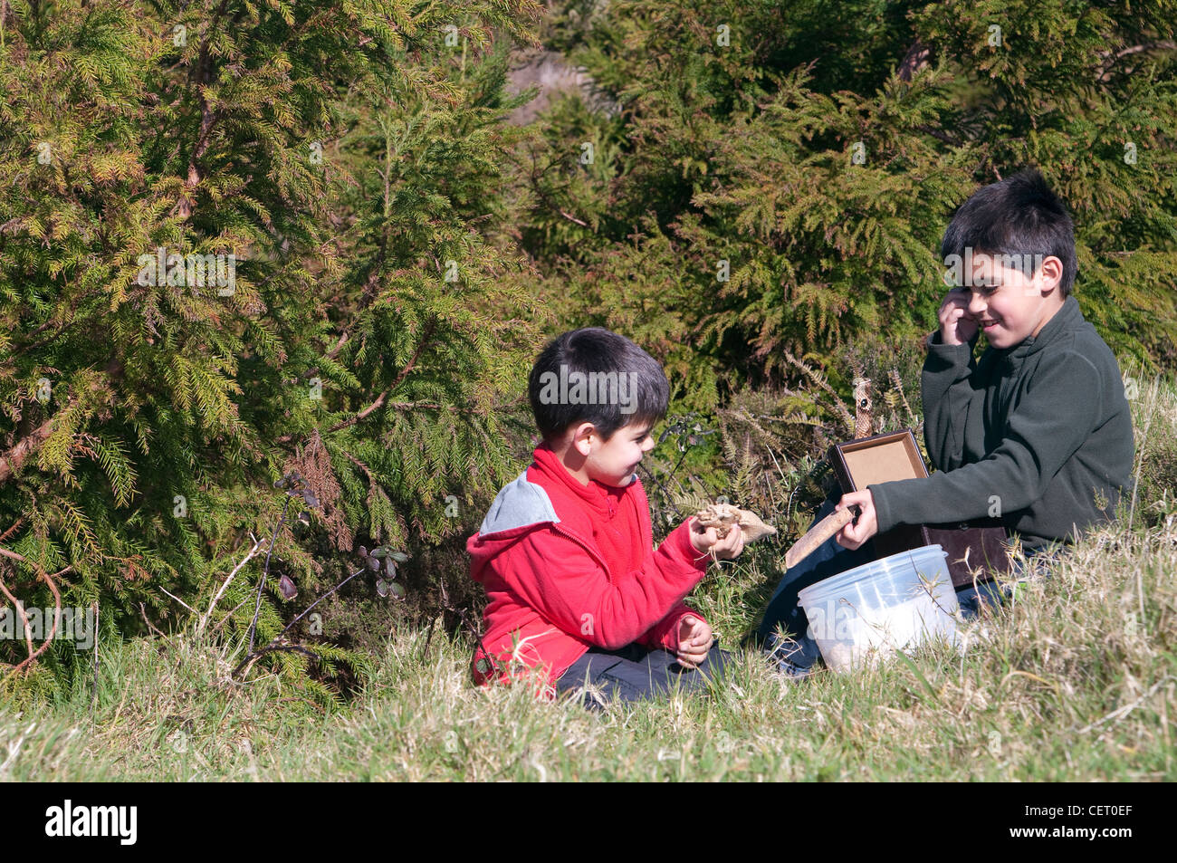 Two boys finding a geocache treasure in the hoods - Stock Image