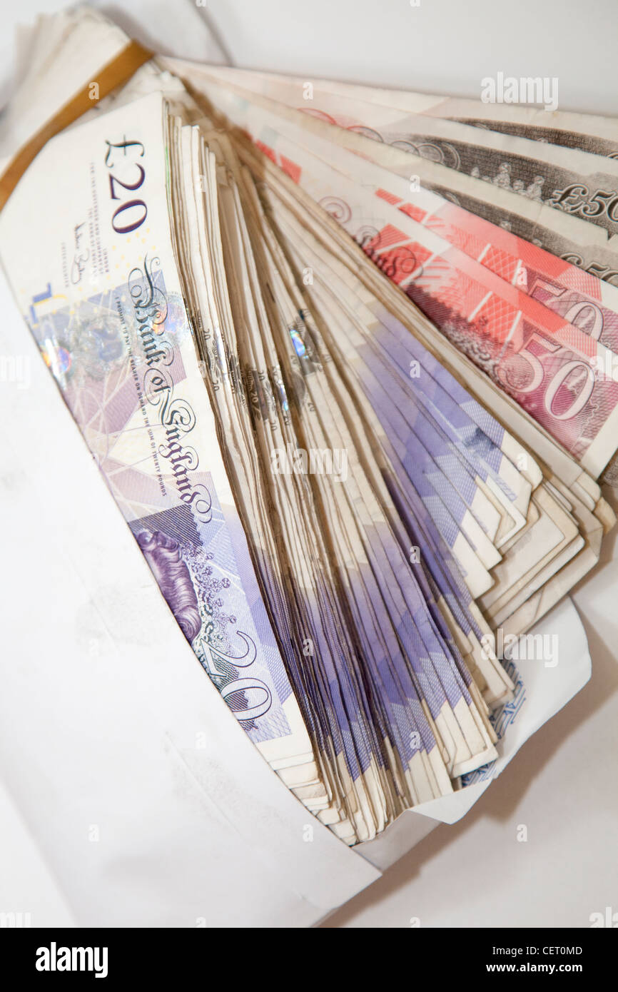 Fifty £50 and twenty £20 pound GBP bank notes in a white envelope England UK - Stock Image