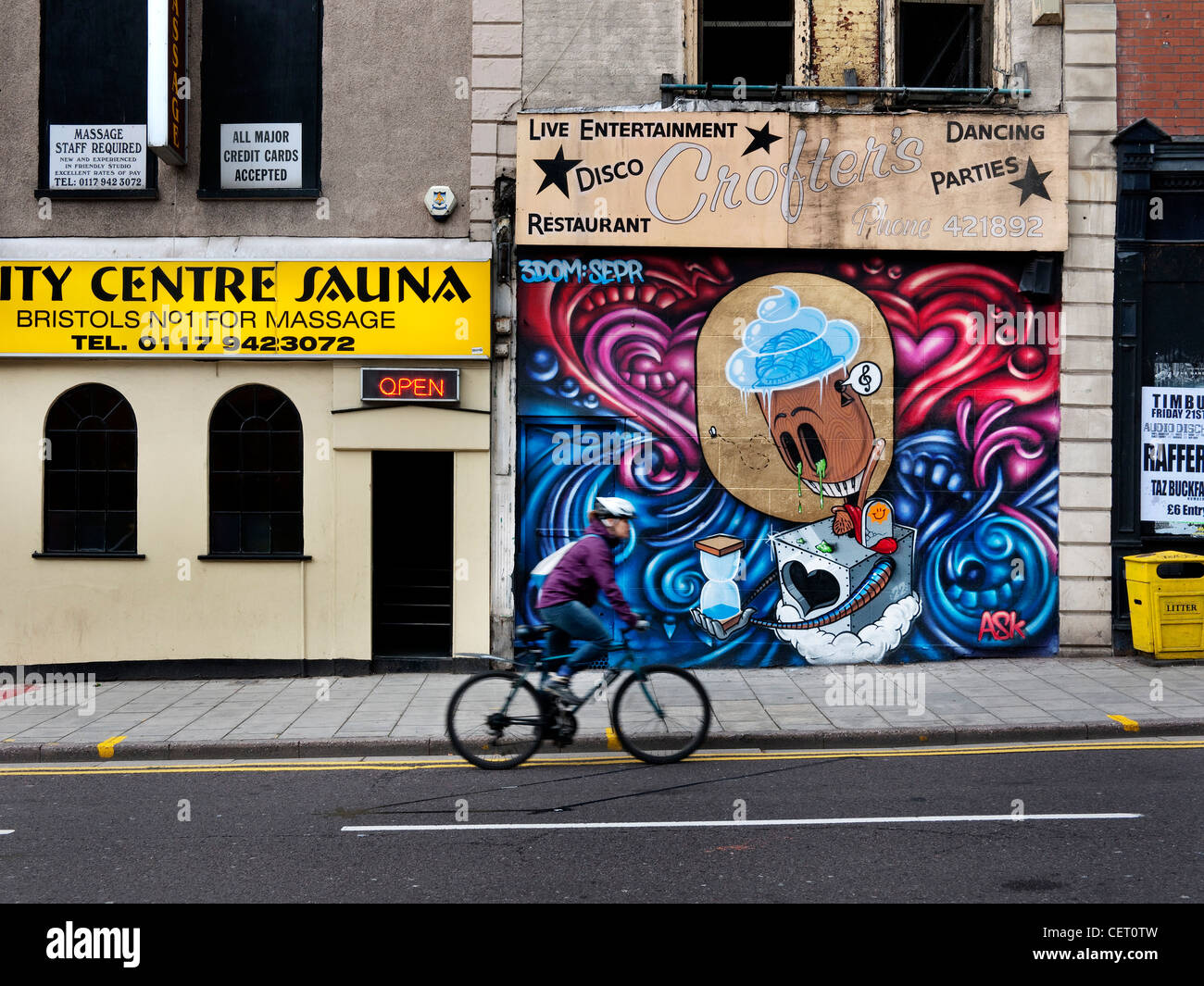 Cyclist Riding Past Graffiti On Bristol Boarded Up Shop Stock Image