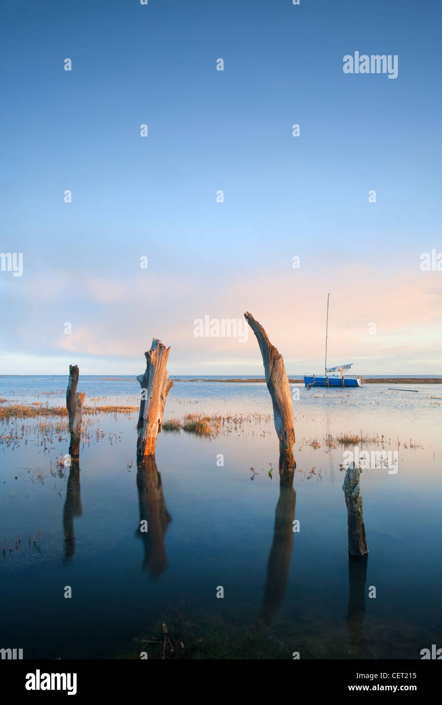 Thornham Harbour and the remains of an ancient wooden pier at high tide on the North Norfolk Coast. - Stock Image