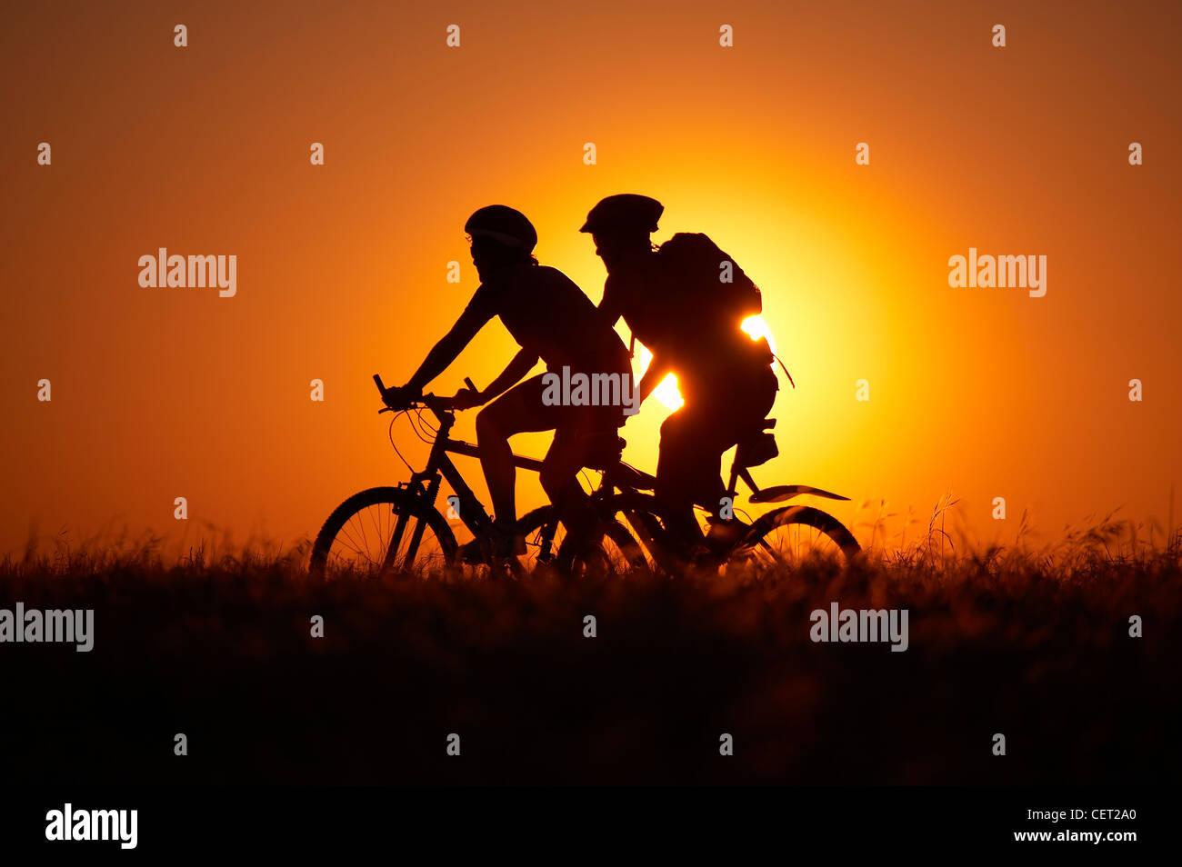 man & woman on mountain bikes cycling on Hambledon Hill above the Blackmore Vale, Dorset, England, UK - Stock Image