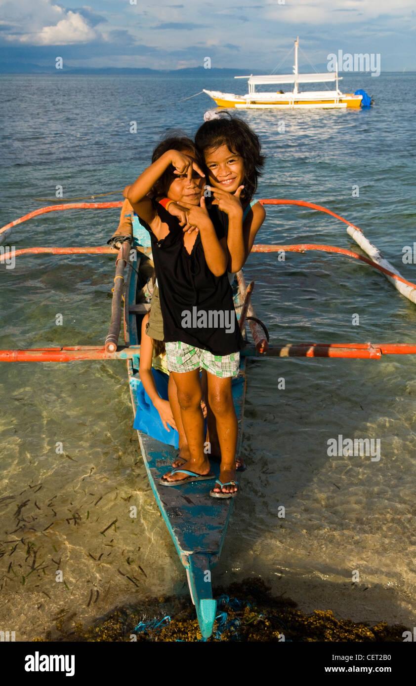 Cute Filipino girls standing on a boat on a beach in Cebu