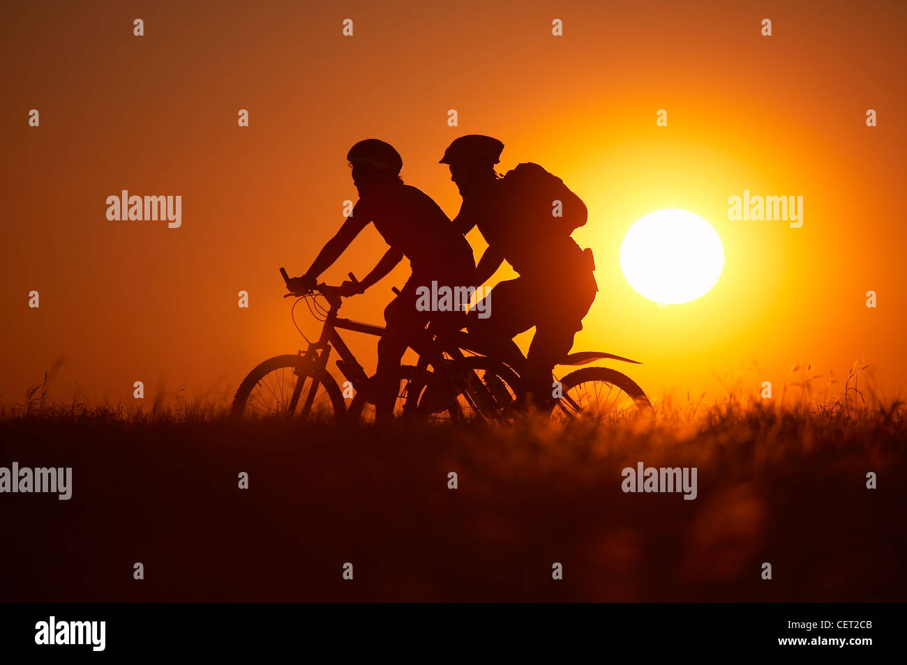 man & woman on mountain bikes cycling on Hambledon Hill above the Blackmore Vale, Dorset, England, UK - Stock Image