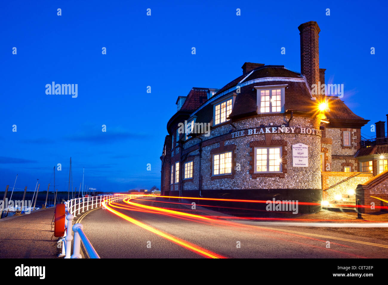 Light trails from cars passing the Blakeney Hotel on the Norfolk Coast at dusk. - Stock Image