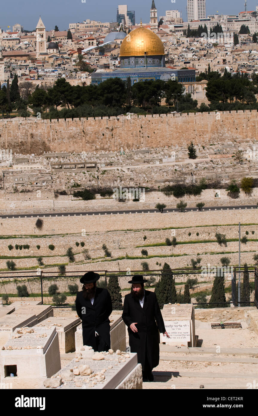 Orthodox Jewish men walking through the Jewish cemetery on the Mount of Olives in Jerusalem. Stock Photo