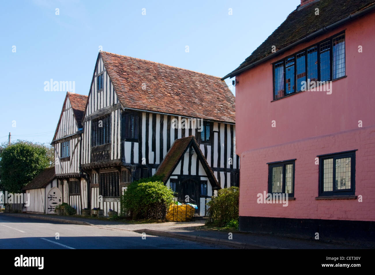 Historical half-timbered houses by a road in the village of Stratford St Mary. - Stock Image