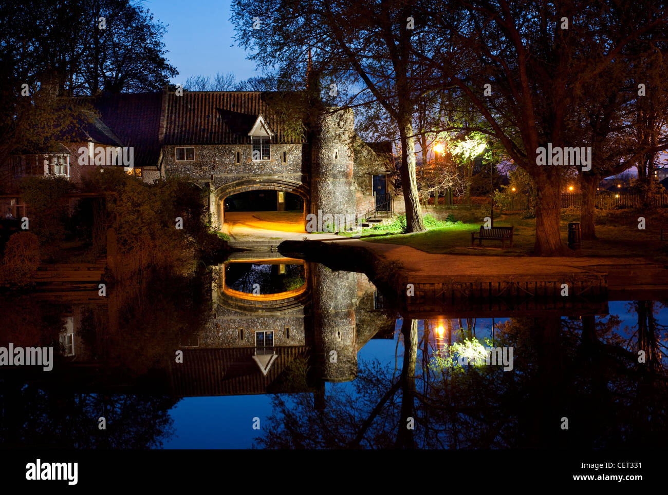 Pulls Ferry, once a 15th century watergate on the River Wensum, illuminated at night. - Stock Image