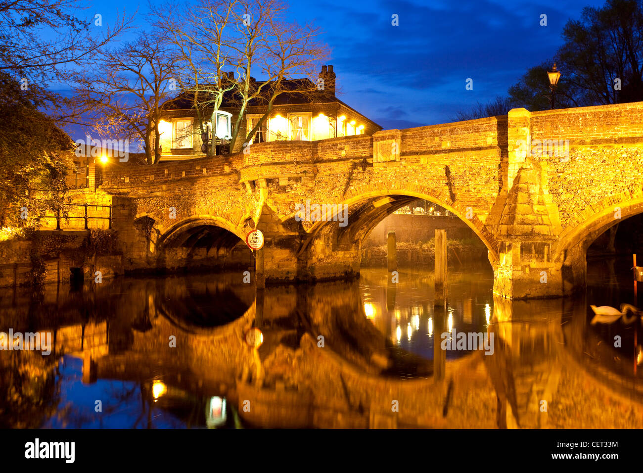 The medieval Bishop Bridge over the River Wensum at night. The bridge was built in 1340 and is one of the oldest - Stock Image