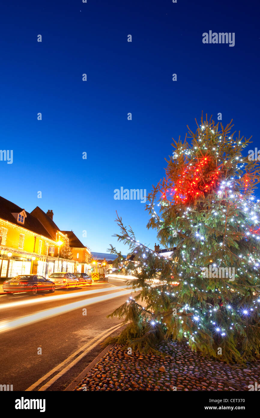Light trails from traffic passing a Christmas tree with decorations by the side of the road in the Georgian market - Stock Image