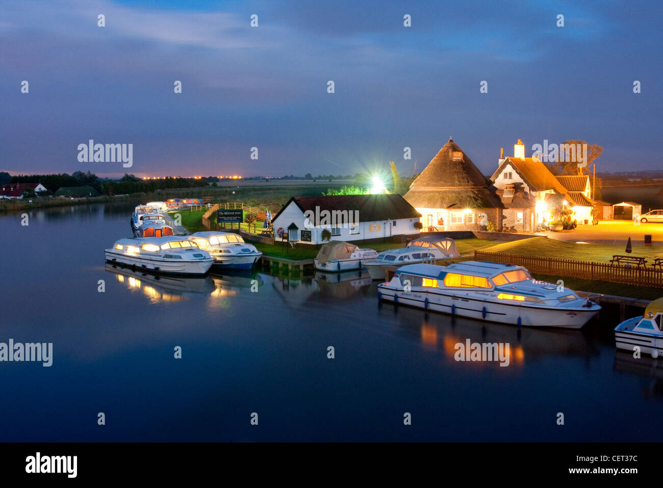 Boats moored outside The Bridge Inn on the Norfolk Broads. - Stock Image
