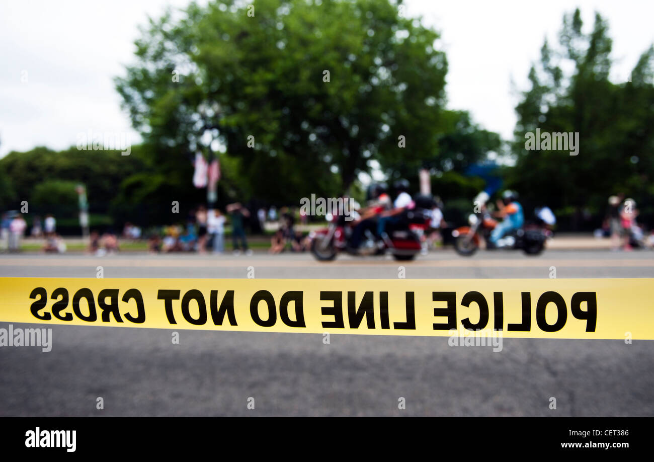 Police Line Do Not Cross, Police tape in downtown Washington DC with motorcycles in background. - Stock Image