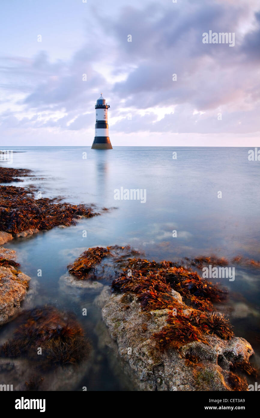 A view of Penmon Lighthouse at dawn on the coast of Anglesey in North Wales. - Stock Image
