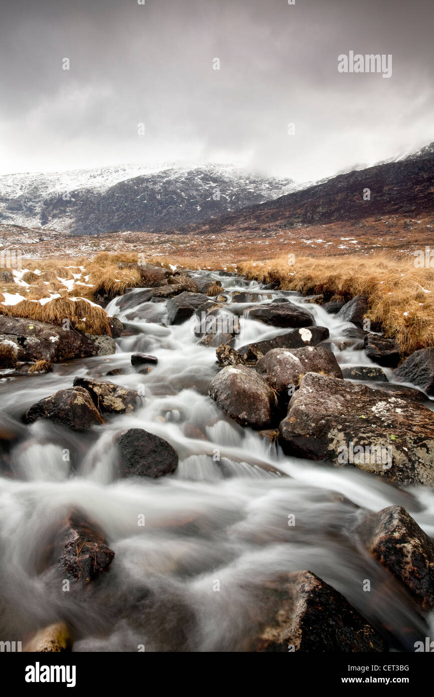 Water flowing down from mountains over rocks in the Snowdonia National Park in Winter. - Stock Image