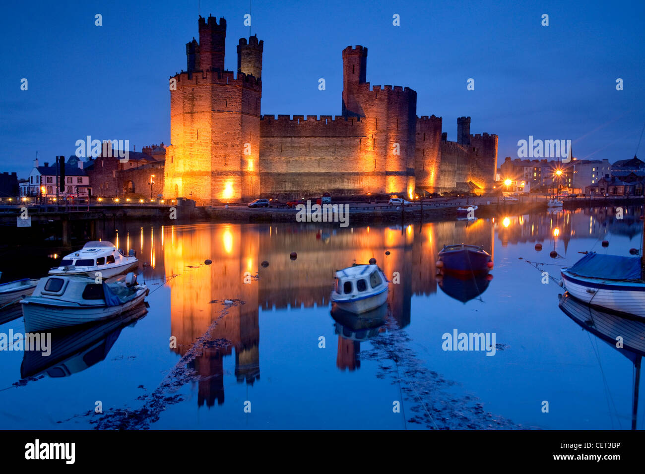 Caernarfon Castle at the mouth of the Seiont river at dusk. Stock Photo