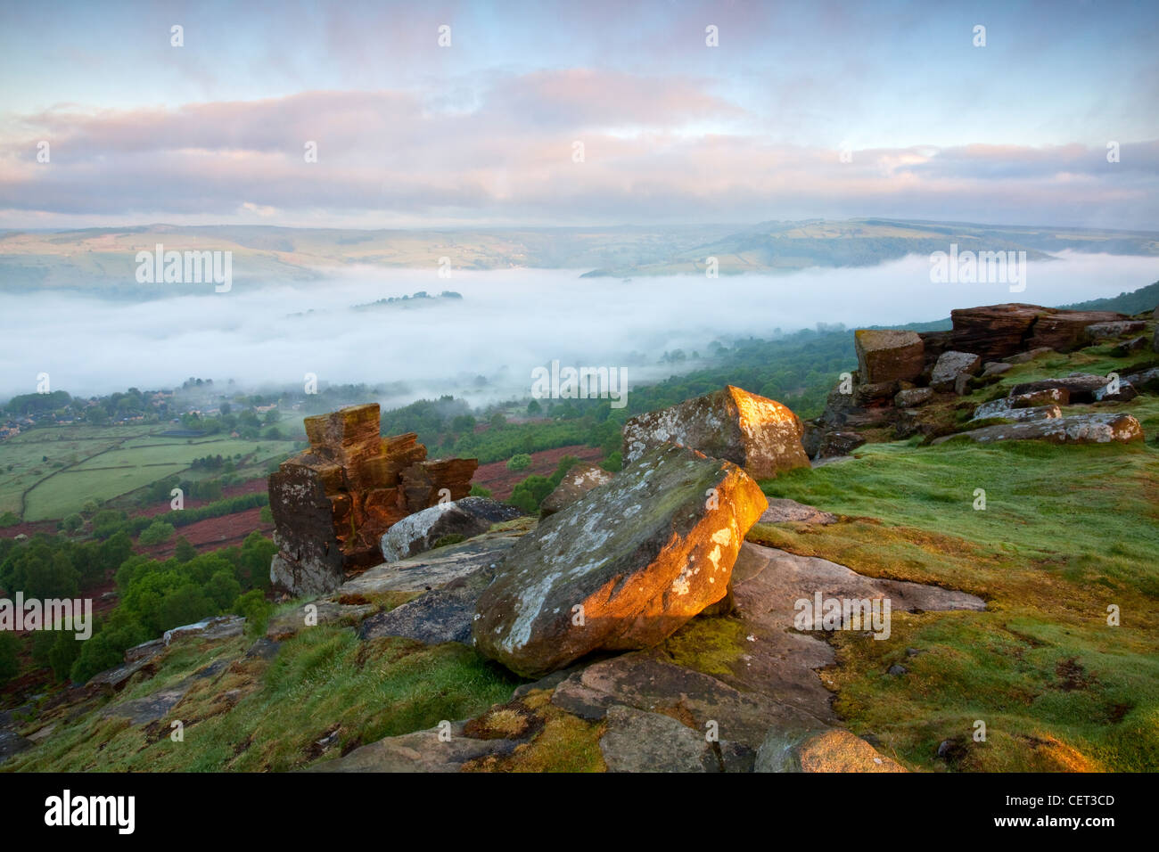 Mist over the village of Calver viewed at first light from Curbar Edge in the Peak District National Park. - Stock Image
