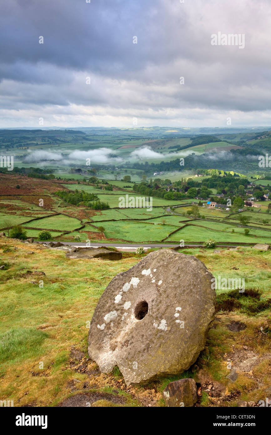 View at dawn from an abandoned millstone on Curbar edge to low lying mist in the valley below. - Stock Image