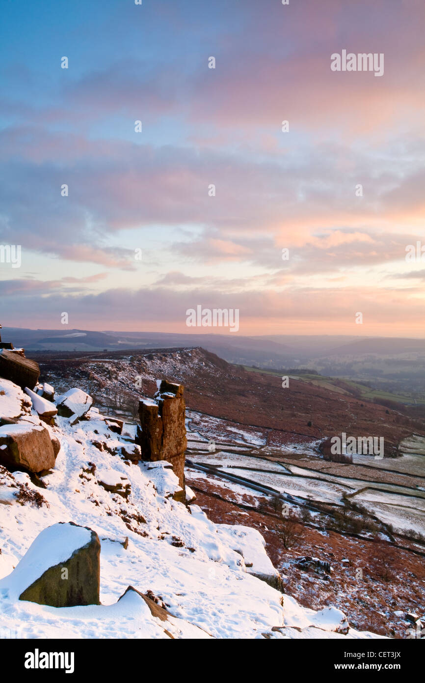Curbar Edge and the Pinnacle rock illuminated by the last rays of the setting sun in the Peak District National - Stock Image
