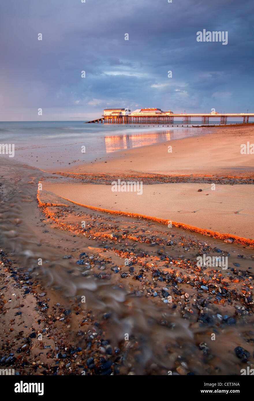 Stormy light over Cromer Pier shortly before sunset on the North Norfolk Coast. - Stock Image