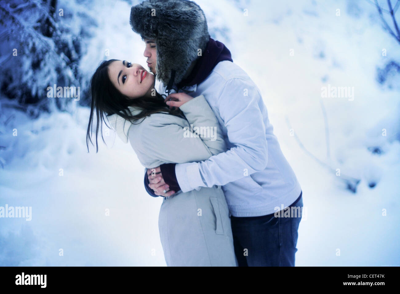 Young adult couple in winter embrace outdoors in snow - Stock Image