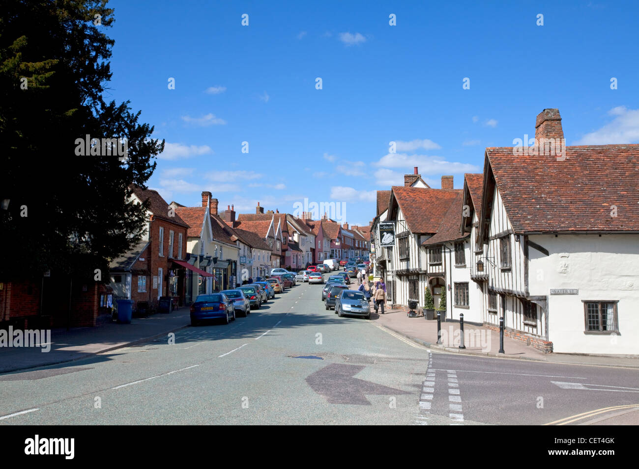 The main road running past historic half-timbered buildings in the village of Lavenham. - Stock Image