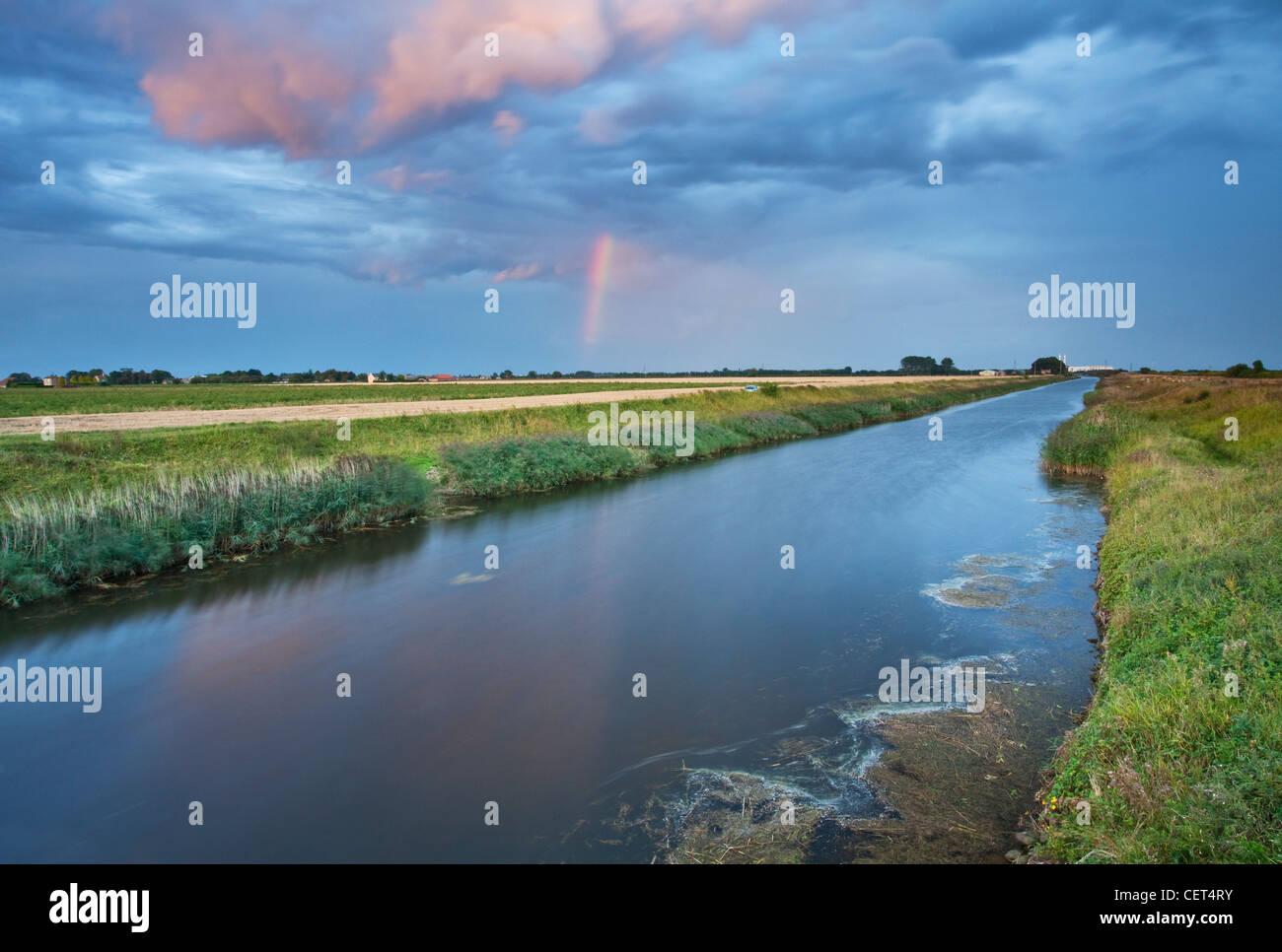 A rainbow appears shortly before sunset over the South Holland Main Drain in Lincolnshire. - Stock Image