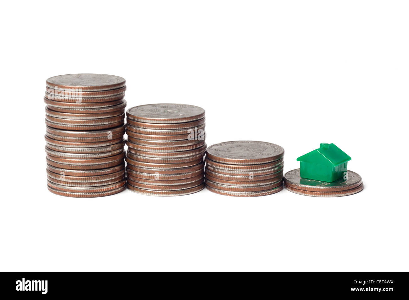 Toys house and pile of coins representing downgrade to a smaller home Stock Photo