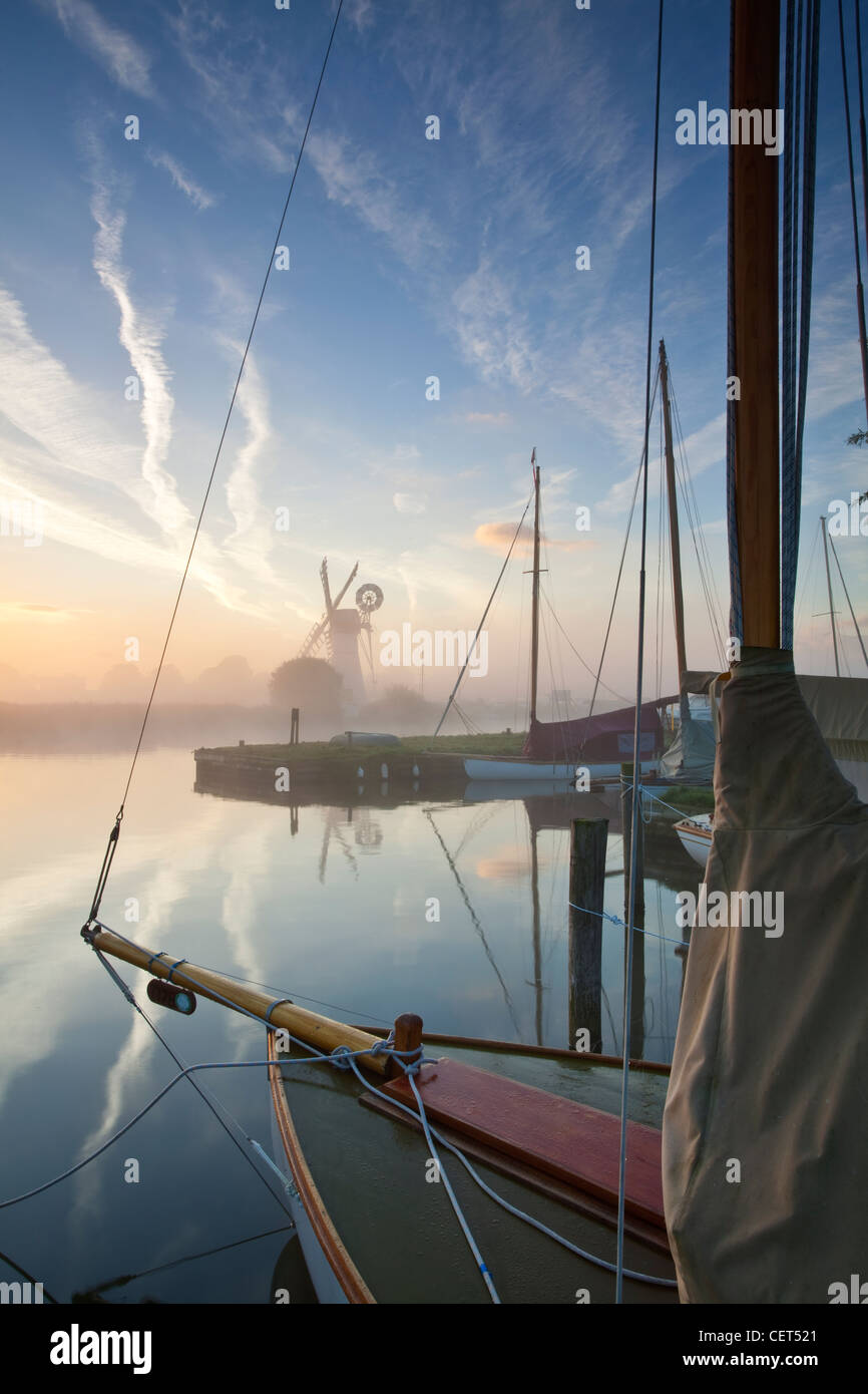 View over the bow of a sailing boat on the River Thurne through dawn mist towards Thurne drainage mill on the Norfolk - Stock Image