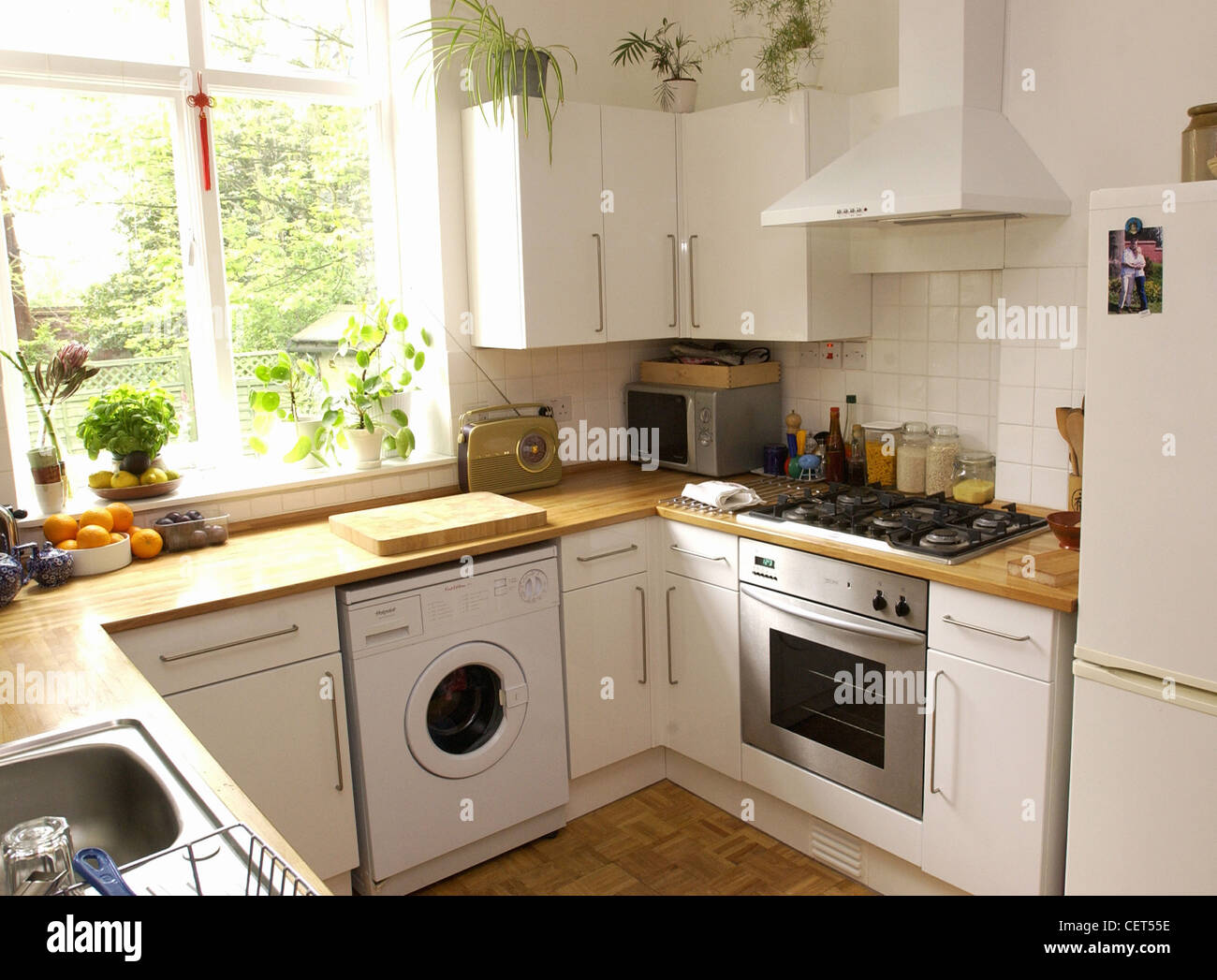Renovated Flat Interiimage Of A U Shaped Kitchen White Tiled Walls, Wood  Worktops, Stailess Steel Oven And Sink, Five Gas