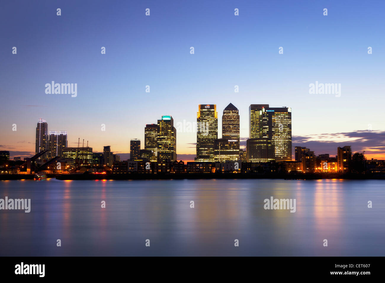 Canary Wharf at Dusk, stitch panoramic of Canary Wharf the light coming on and reflecting in the Thames. - Stock Image