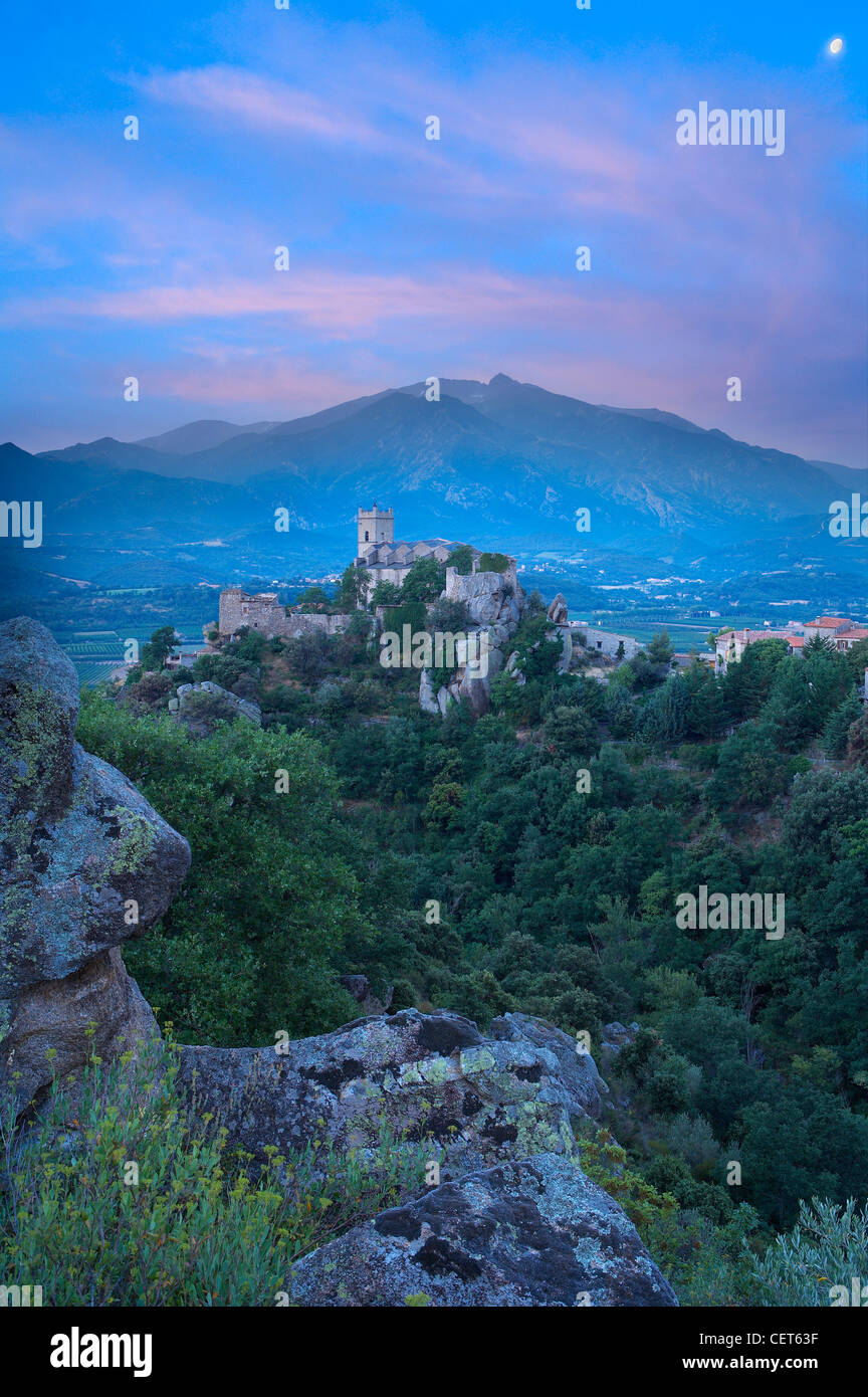 the village of Eus perched on a hilltop with the Pic de Canigou beyond, the Pyrenees, Languedoc-Rousillon, France - Stock Image