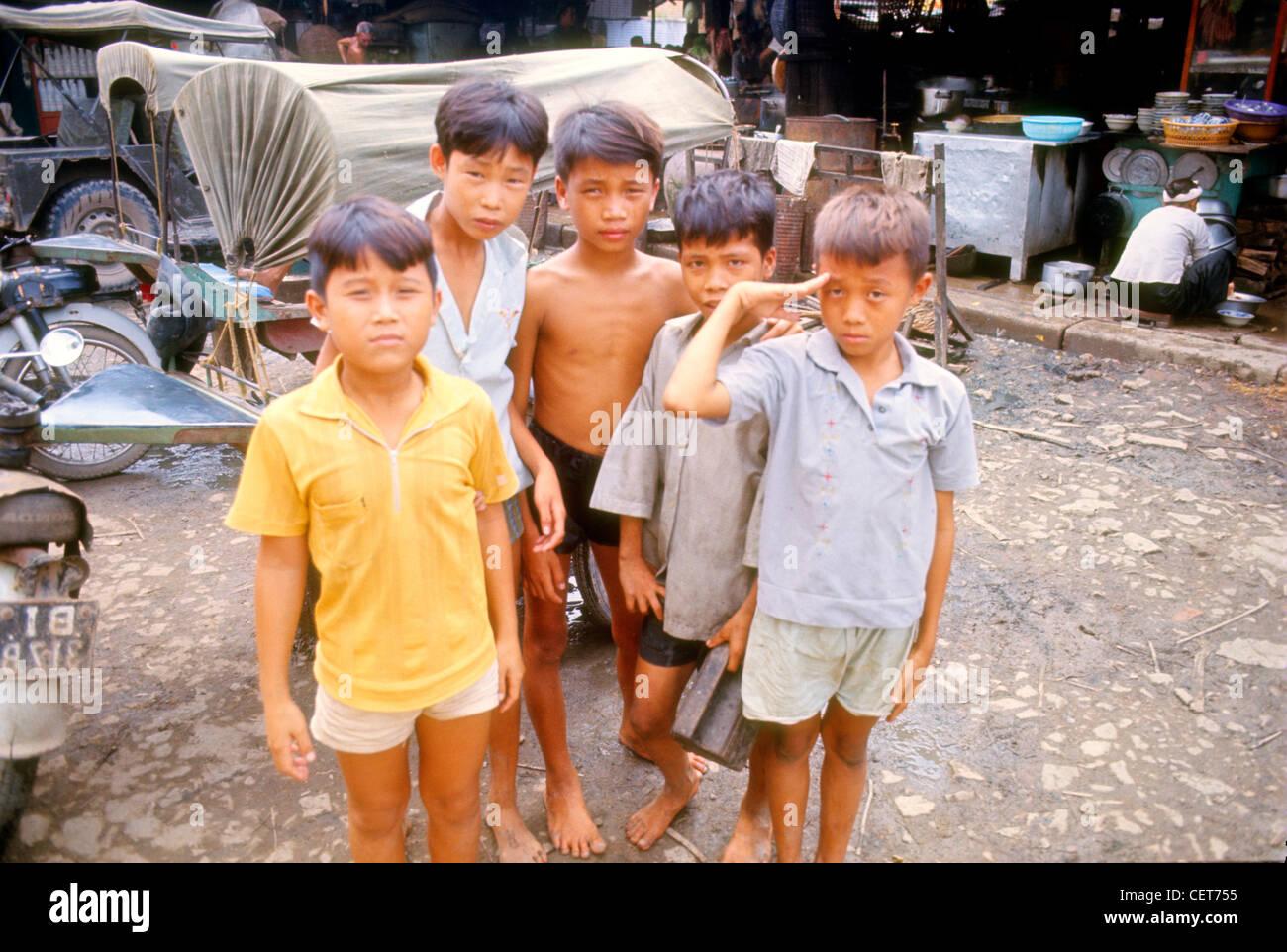 Children in market saluting american during the Vietnam War. - Stock Image