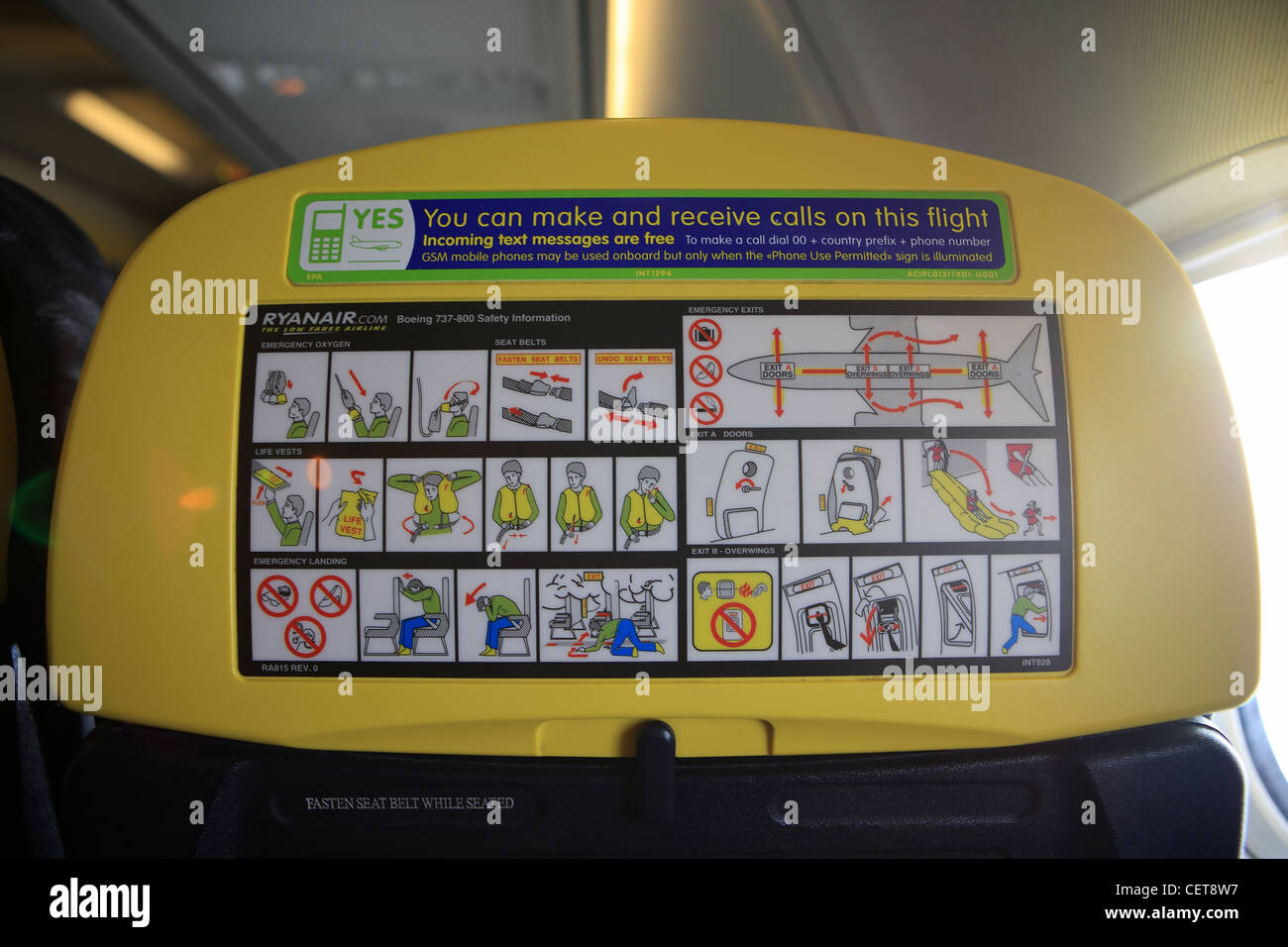 Safety and mobile phone instructions on the back of seats on a Ryanair plane - Stock Image