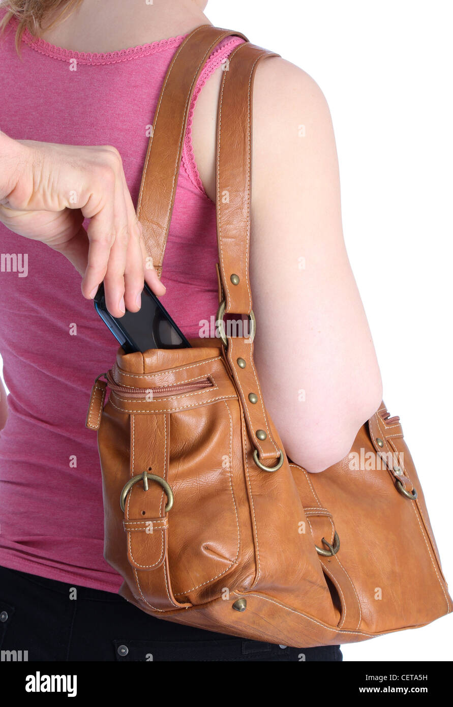 Pickpocketing a mobile out of a handbag of a woman - Stock Image