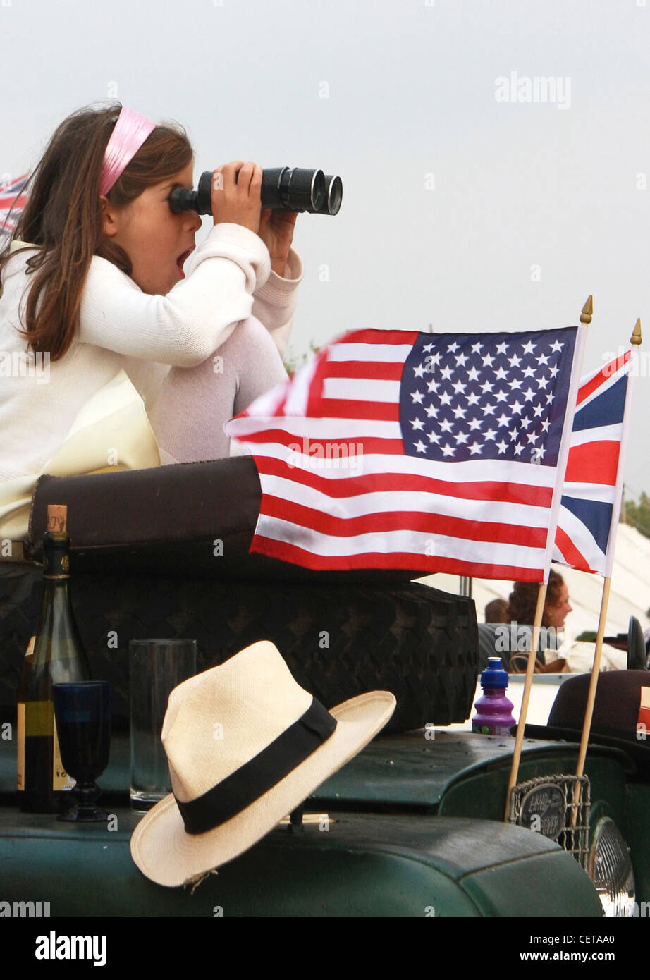 Girl with binoculars watching car races at Goodwood Revival. - Stock Image