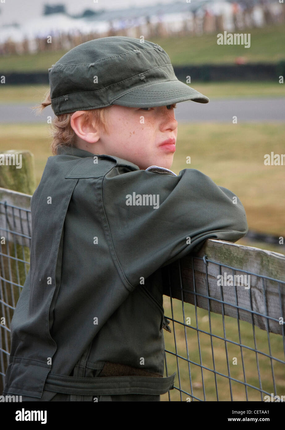 Young boy in jumpsuit watching car races at Goodwood Revival. - Stock Image