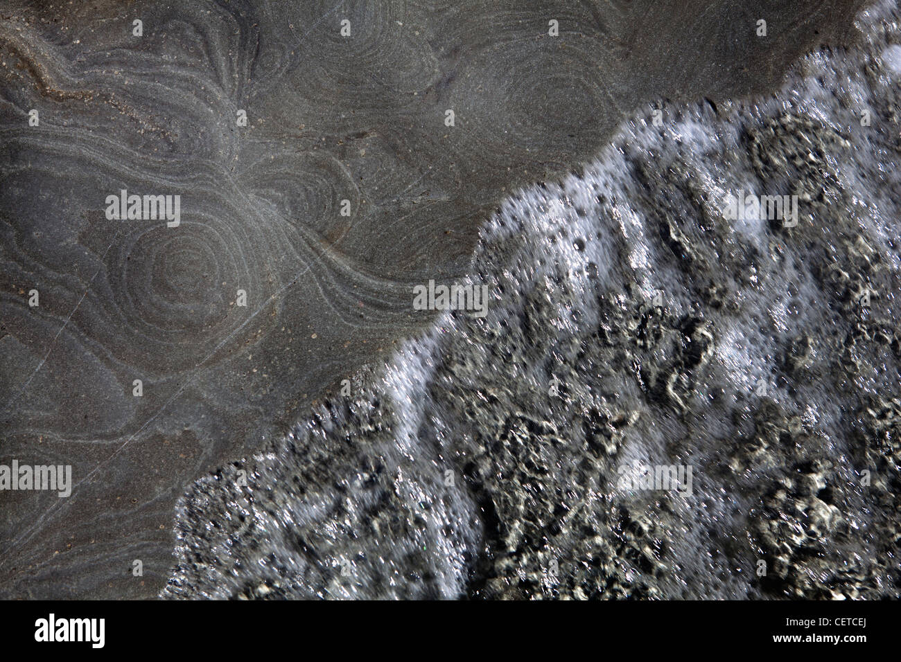 tide washing rocks - Stock Image