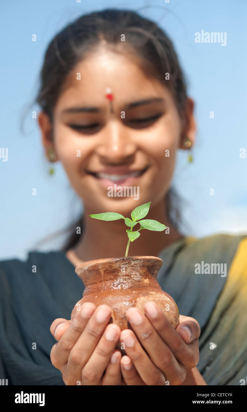 Indian teenage girl holding a plant seedling in a clay pot. India - Stock Image