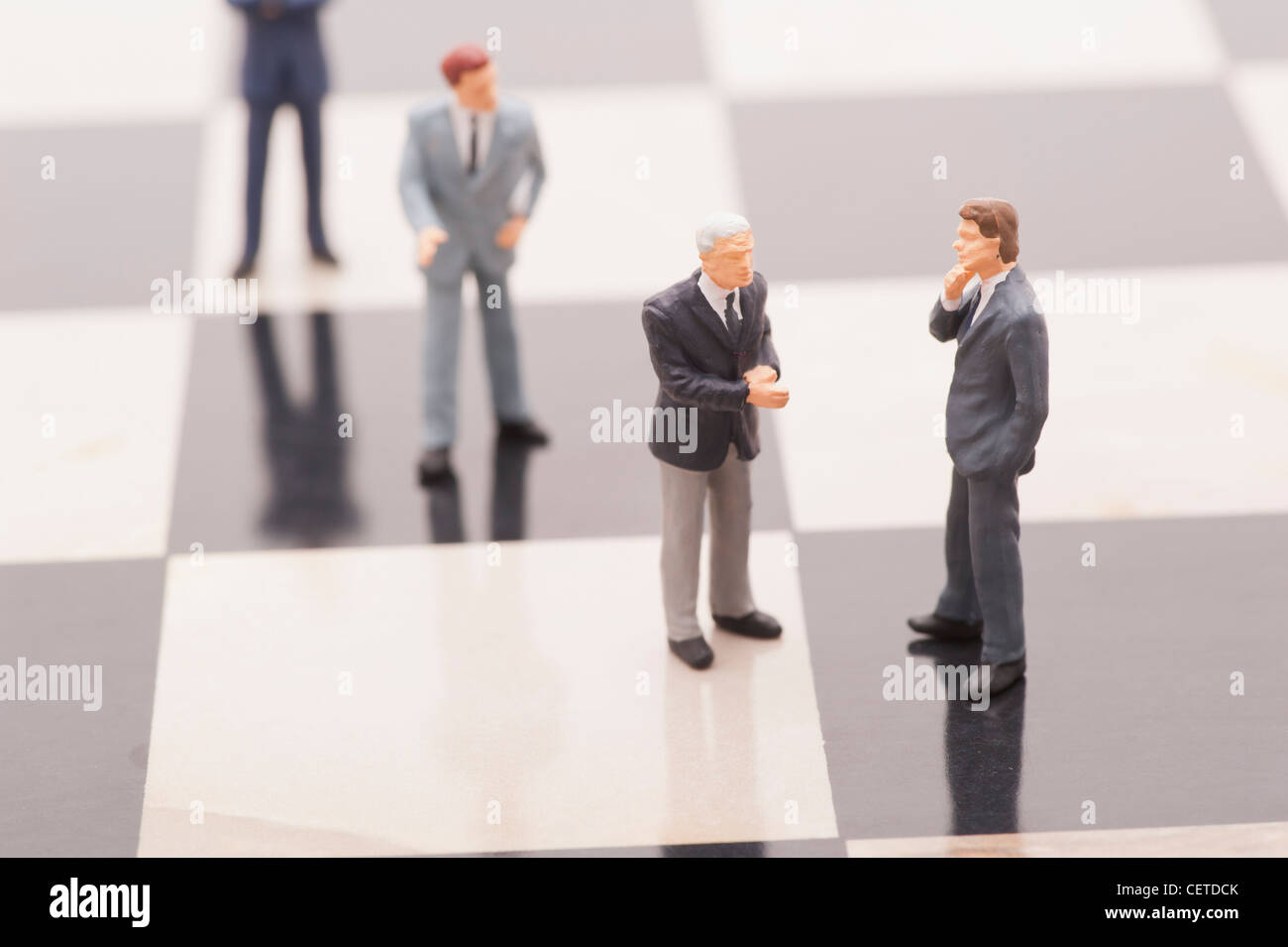 Figurines of businessmen in line to shake hands - Stock Image